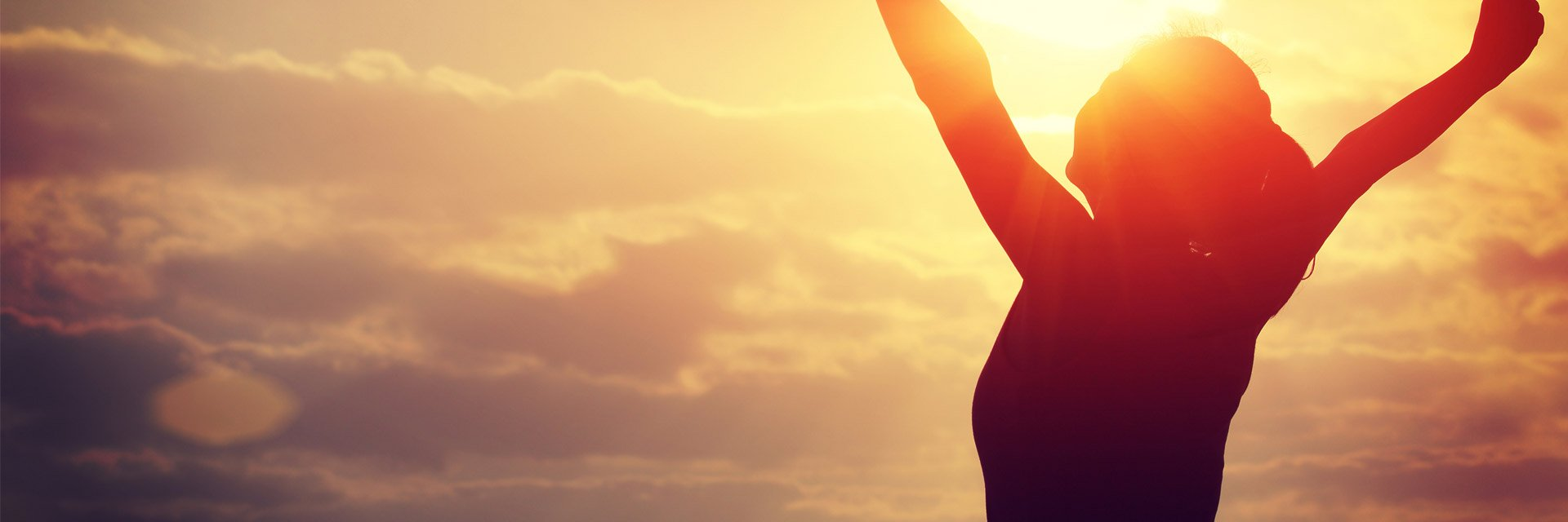 Woman with arms outstretched at sunrise