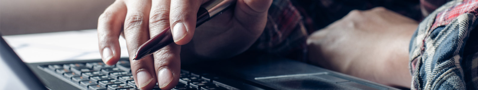 Close up of a man's hand holding a pen above a laptop keyboard