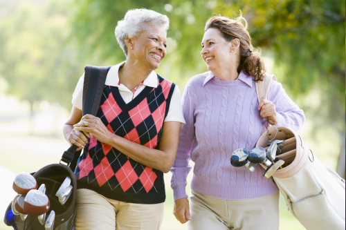 Two woman carrying golf bags